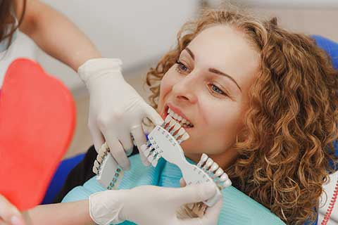 woman sites in a dental chair while the dentist compares which shade of tooth color matches the patient's teeth